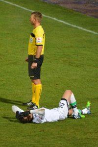 Ein gefoulter Fussballspieler liegt am Boden